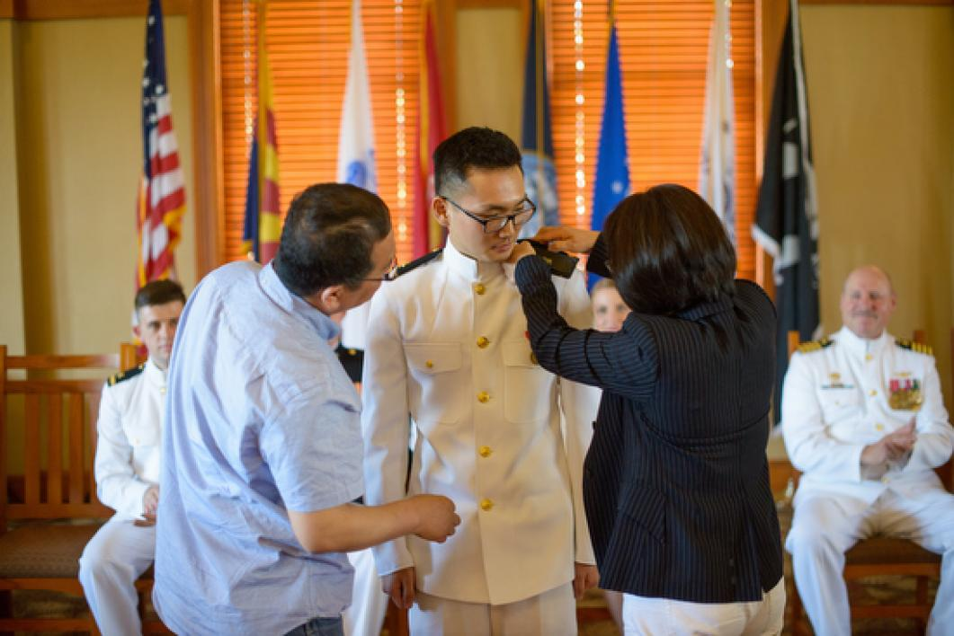 parents pinning ensign rank on son during ASU Navy ROTC commissioning ceremony