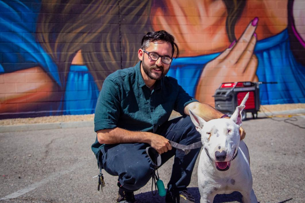 The artist, wearing glasses and a green button-up shirt, crouches on the pavement in front of the mural with his pit bull