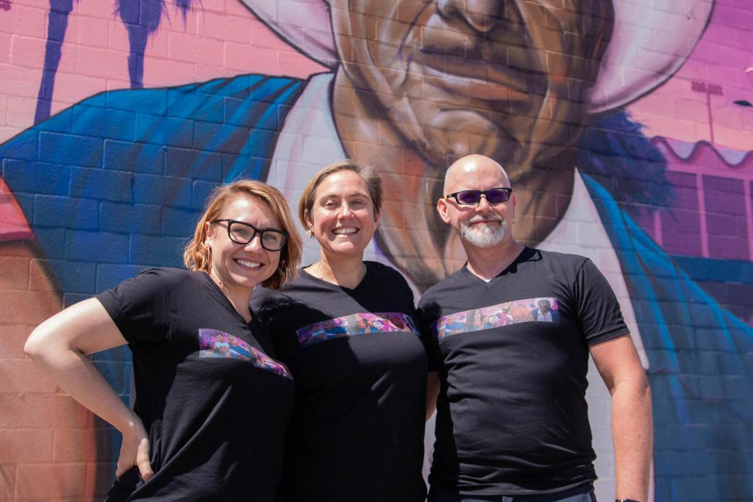 Two females and one male stand in front of the Maryvale mural wearing T-shirts also depicting the mural