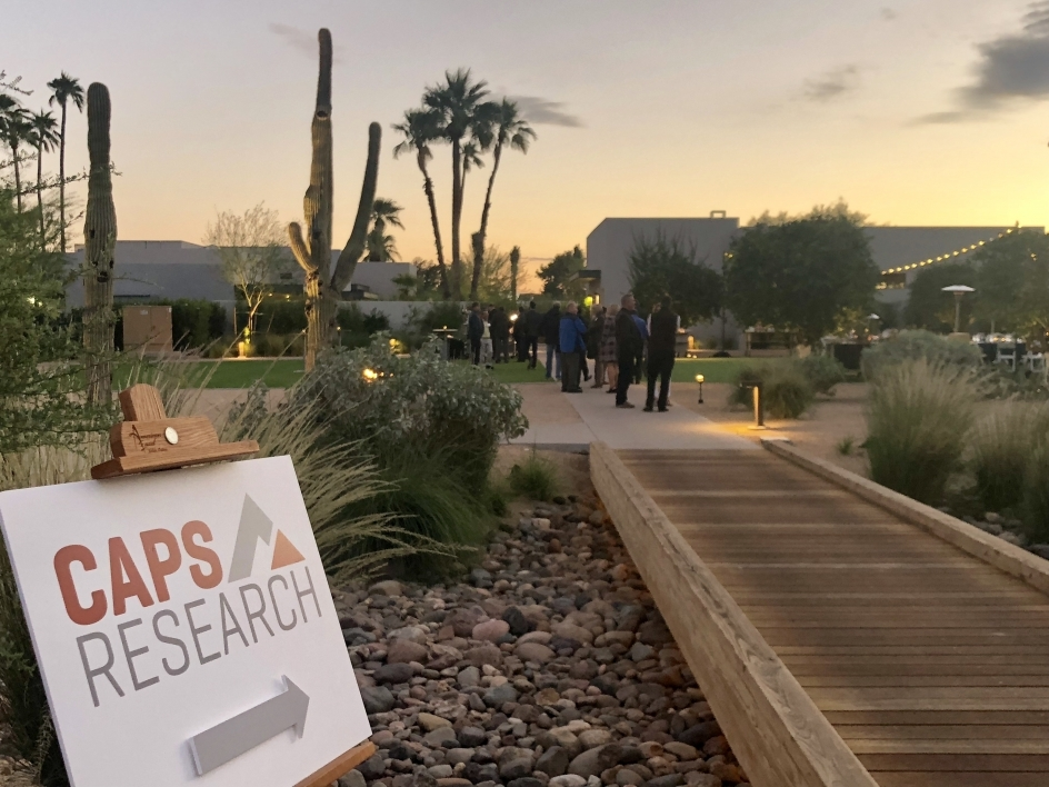 CAPS Research sign in foreground, people at outdoor networking event in background