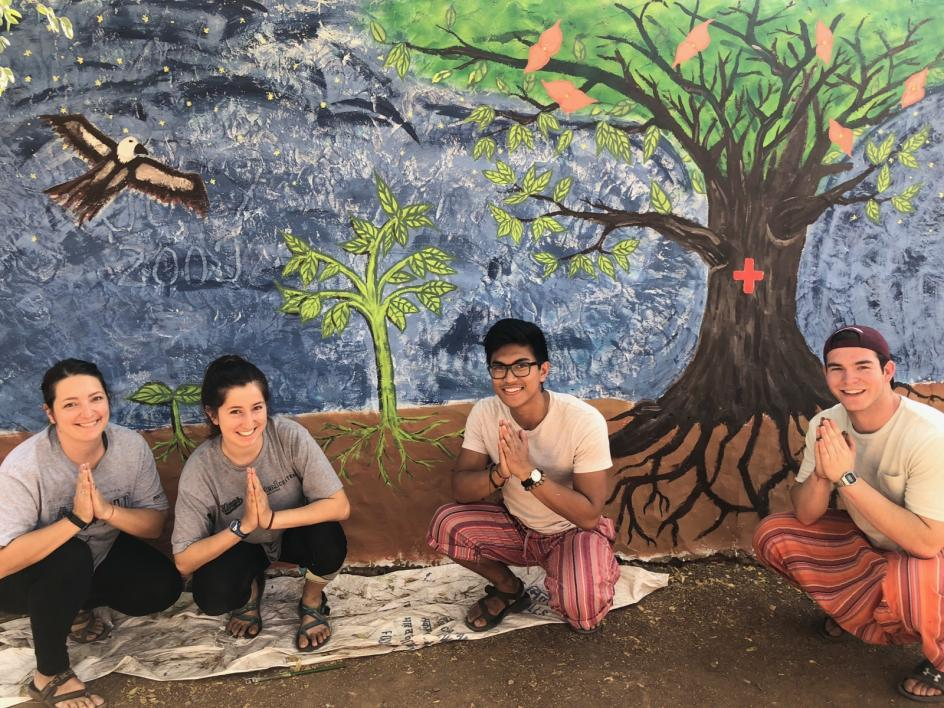 Kirra with 3 other students in front of a mural project in India.