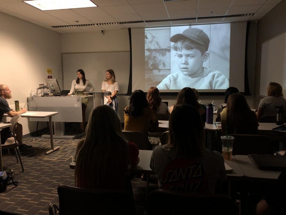 Picture of students presenting a video in the classroom.