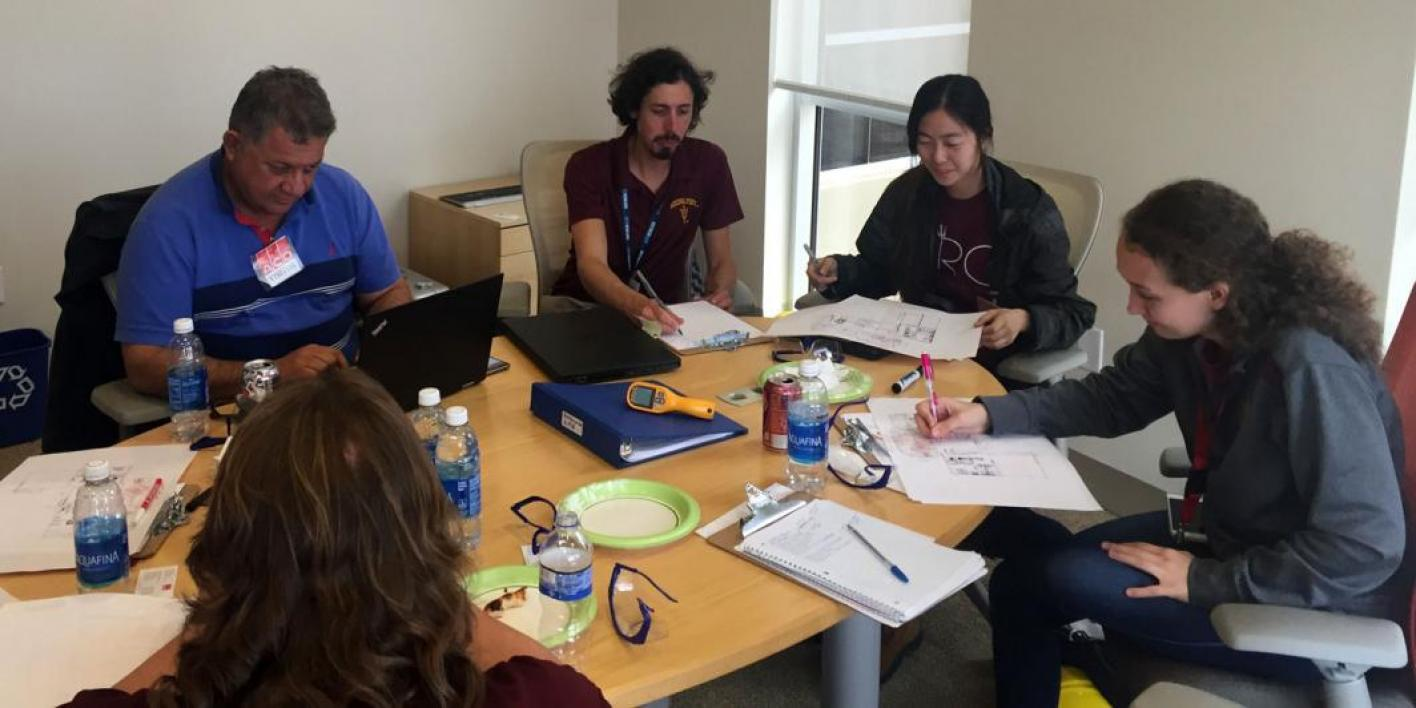 This photo shows a team of students sitting at a table analyzing data from their on-site visit of a manufacturing center.