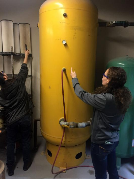 Mechanical engineering undergraduate students Celine Chang and Kaitlin Kreck assess gauge pressure and a name plate at a manufacturing site.