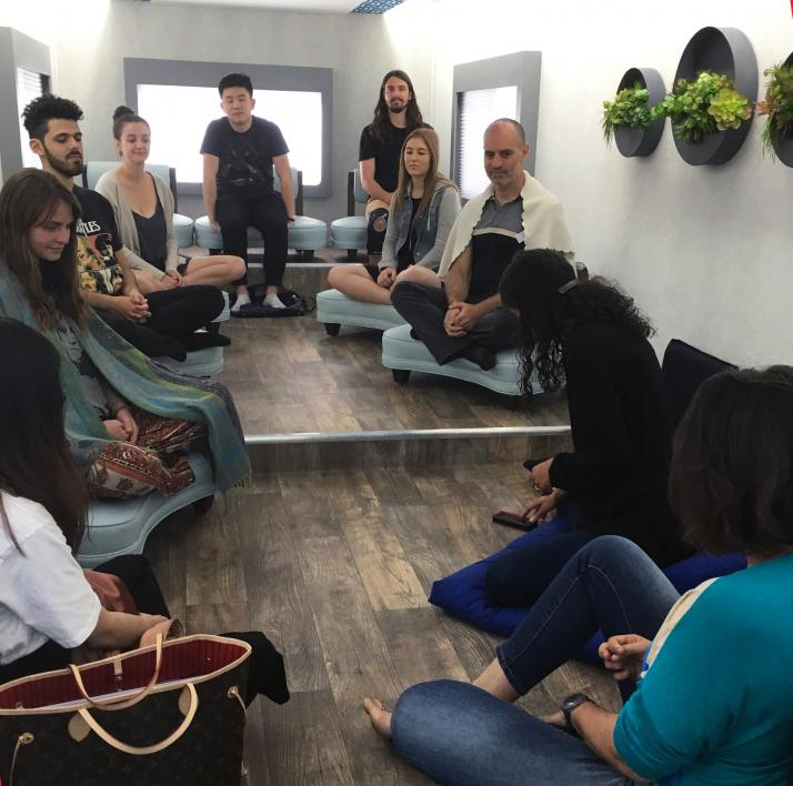 A group sits for a mindfulness session inside the M2 truck