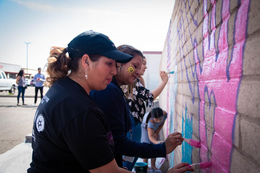 Community members, including adults and kids, a giant pink hand with a heart in the center on a brick wall at the event