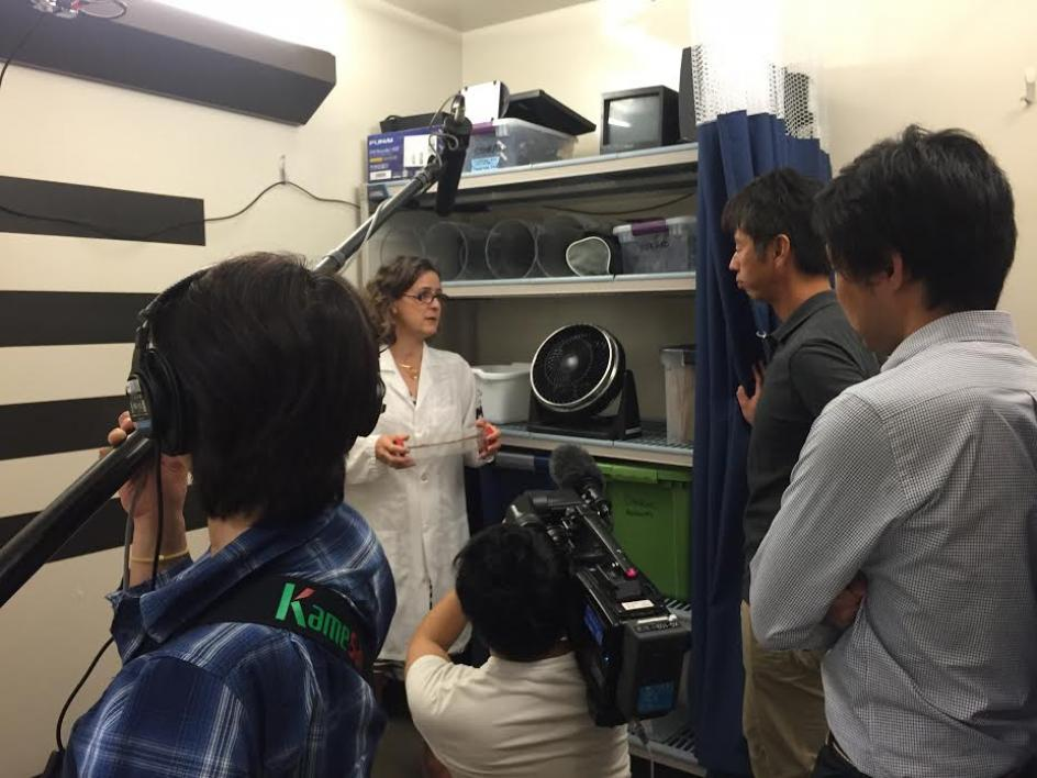 woman showing lab to film crew