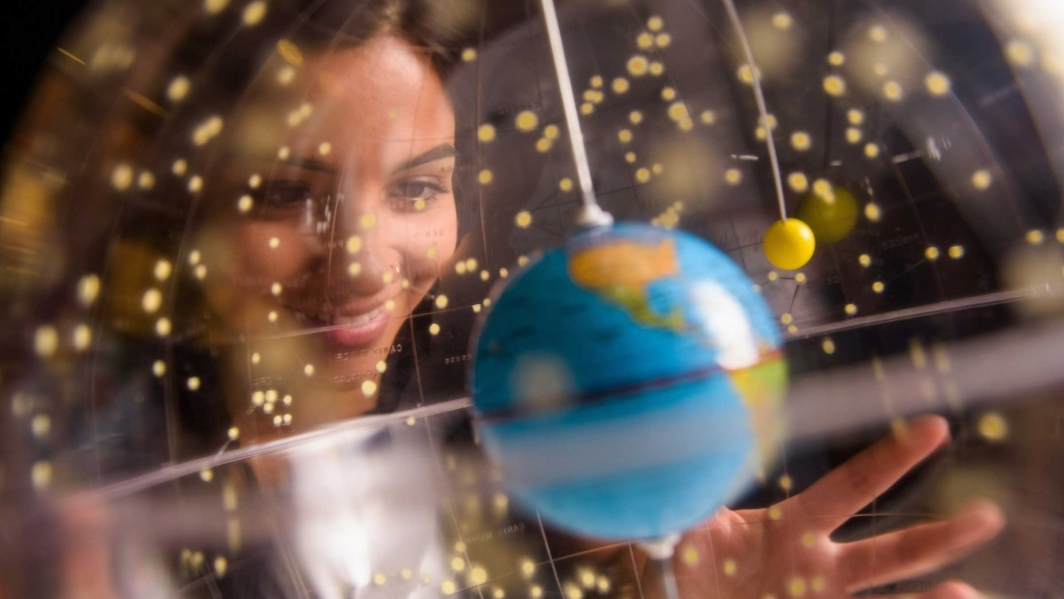 A woman looks through a clear globe at a small Earth
