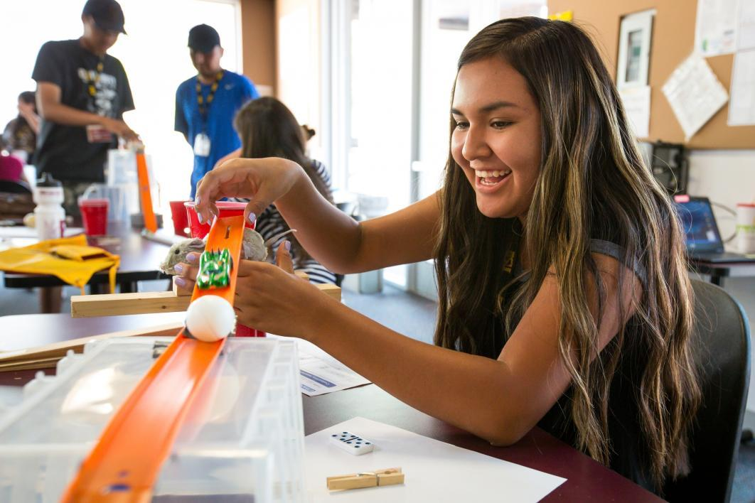 A student plays with a chain-reaction machine at Inspire camp.
