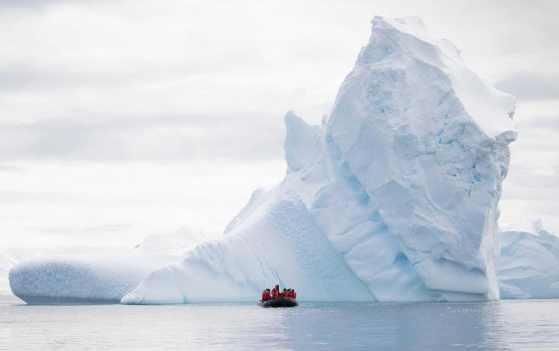 A zodiac boat off in the distance next to a large iceberg