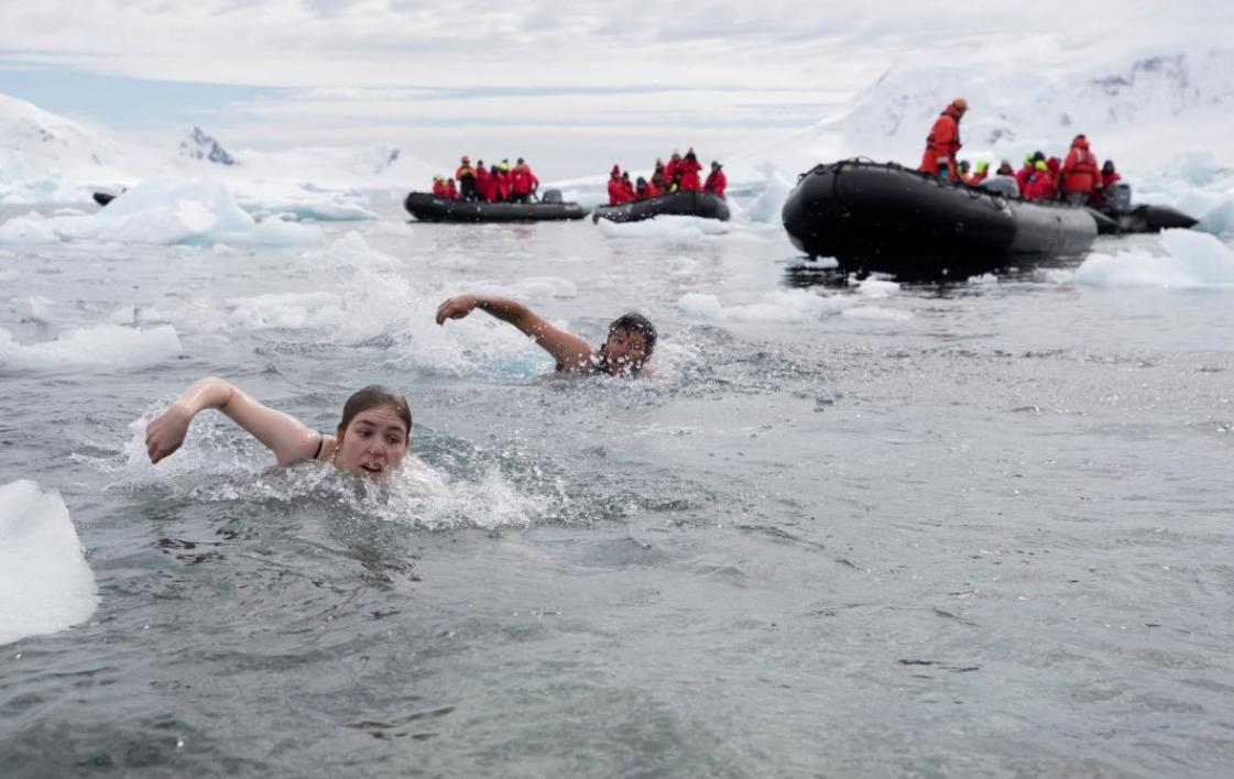Two students swimming in Antarctica amidst doing a polar plunge