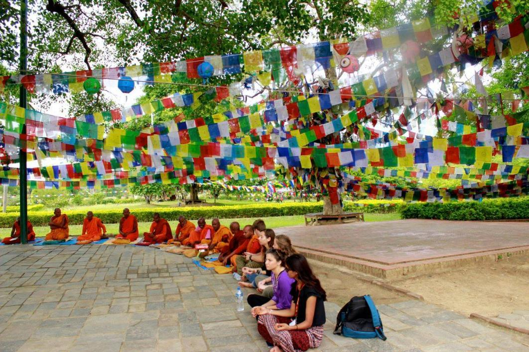 Students sit with Nepali monks under colorful flags