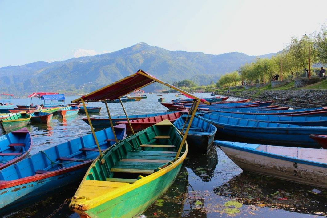Boats sit in Nepali lake with mountains in background