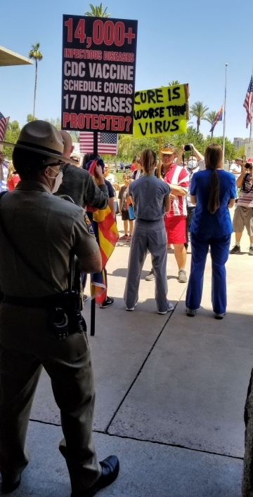 Lauren Leander stands with fellow nurses as protesters address them at the Arizona State Capitol