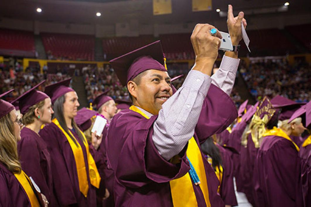 student waving from crowd at convocation