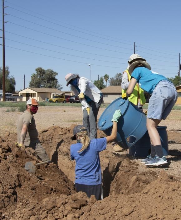 Volunteer hands large plastic bucket to workers in trench