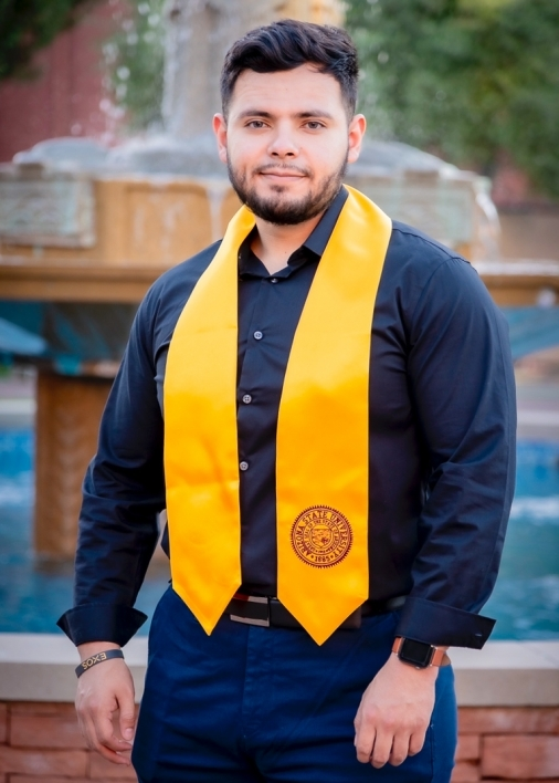 ASU College of Health Solutions graduate Alejandro Lopez wearing a gold sash and standing in front of the fountain at Old Main on ASU's Tempe campus