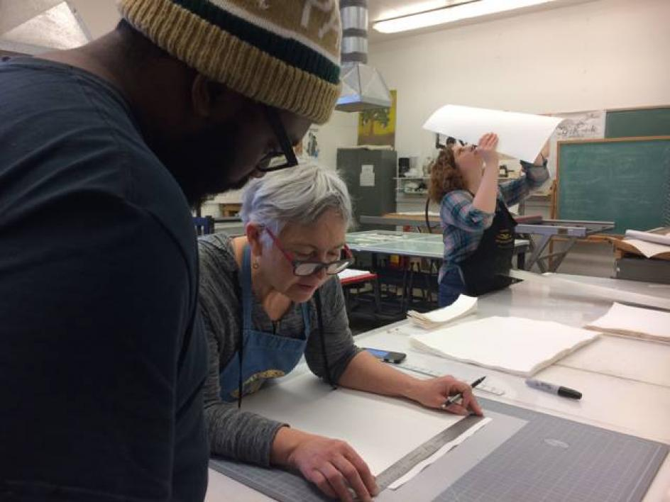 Artist Brenda Mallory works on her piece with students Jonathan Wright and Kelsey Reiman