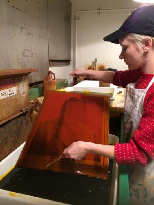 Student Lauren Kelly etching a large photogravure for artist Sarah Sense