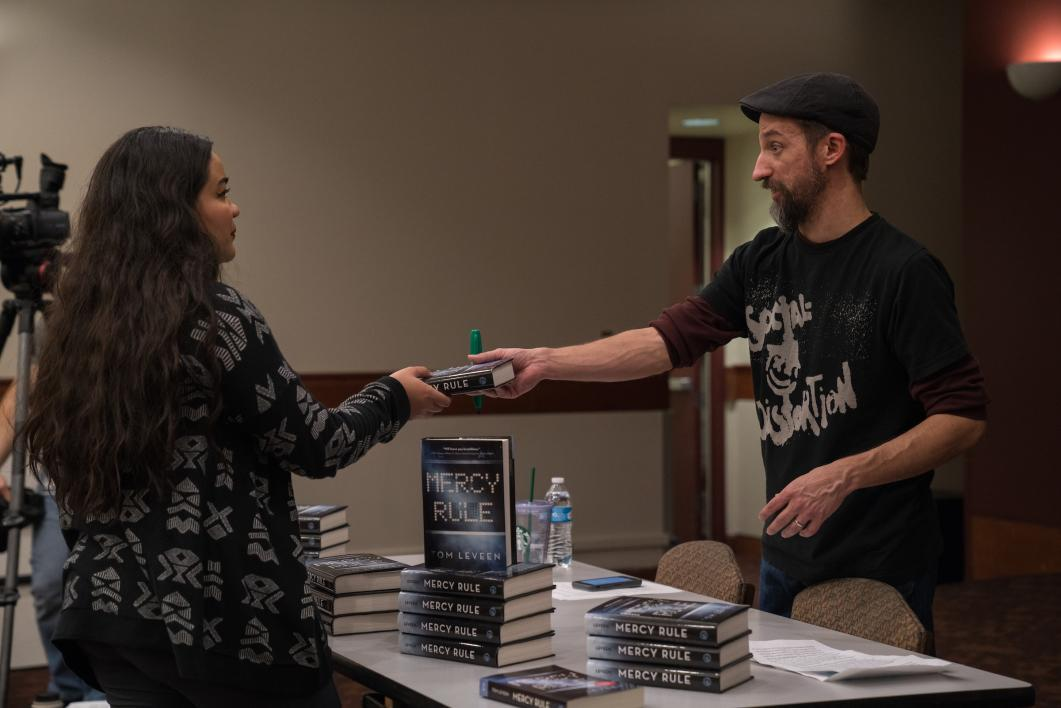 man handing book to woman