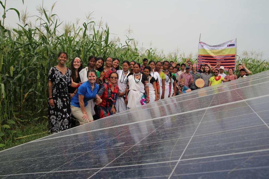 Students stand with Nepali community members next to solar panels