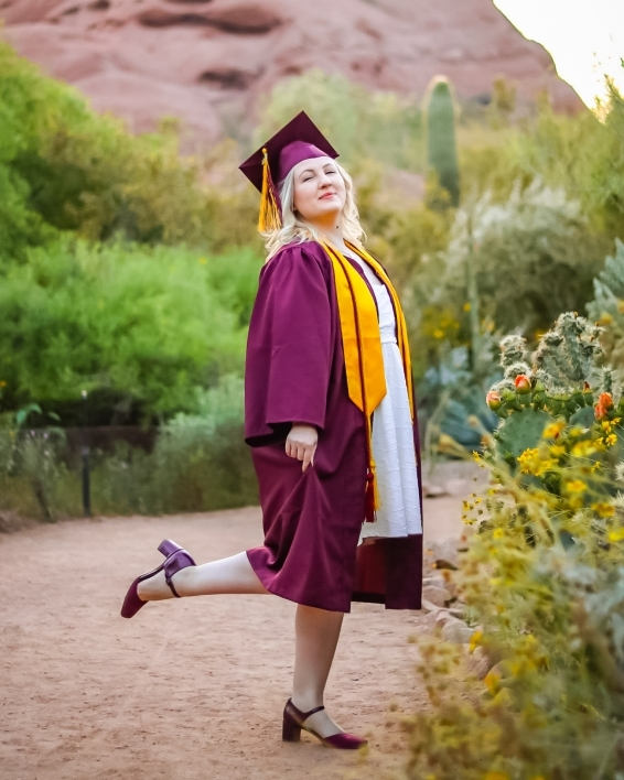 ASU College of Health Solutions graduate Evan Miller wearing her cap and gown while kicking one foot out behind her as she stands in a desert landscape