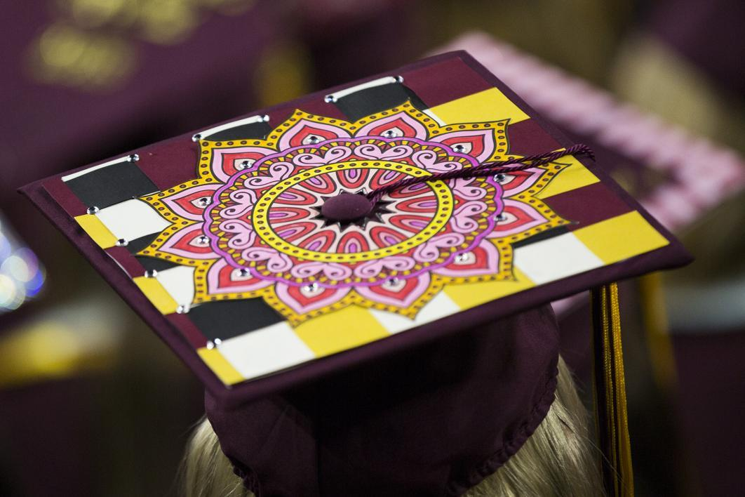 A graduation cap is covered with a pink colored mandala design