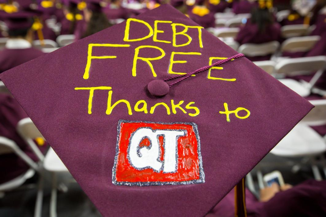 "A graduation cap that says ""Debt Free thanks to QT"""
