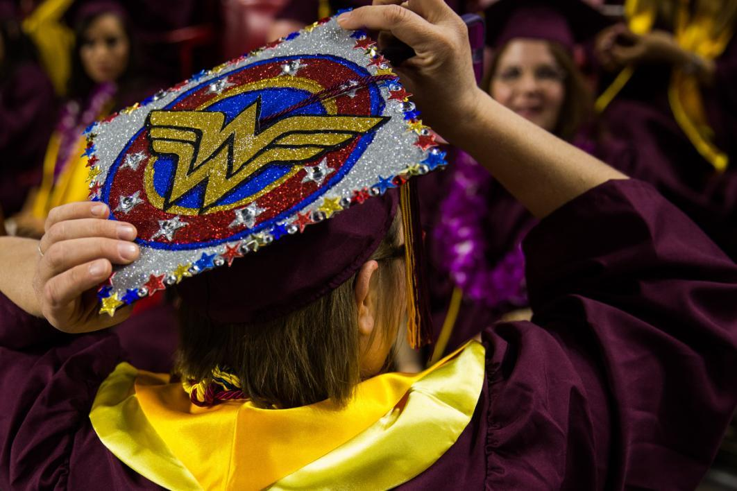 A graduation cap carries the Wonder Woman logo