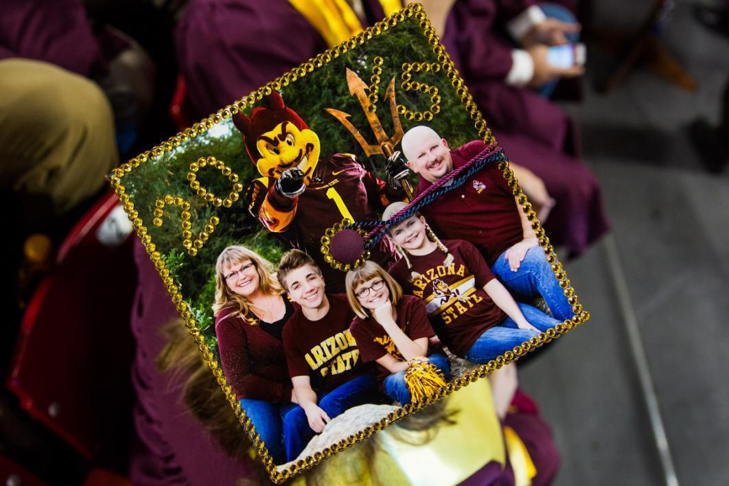 A graduation cap has a family photo with all members wearing maroon and gold