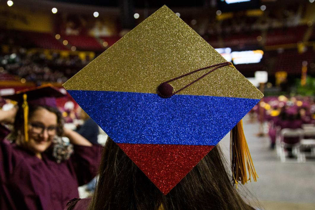 A graduation cap shows a Colombian flag