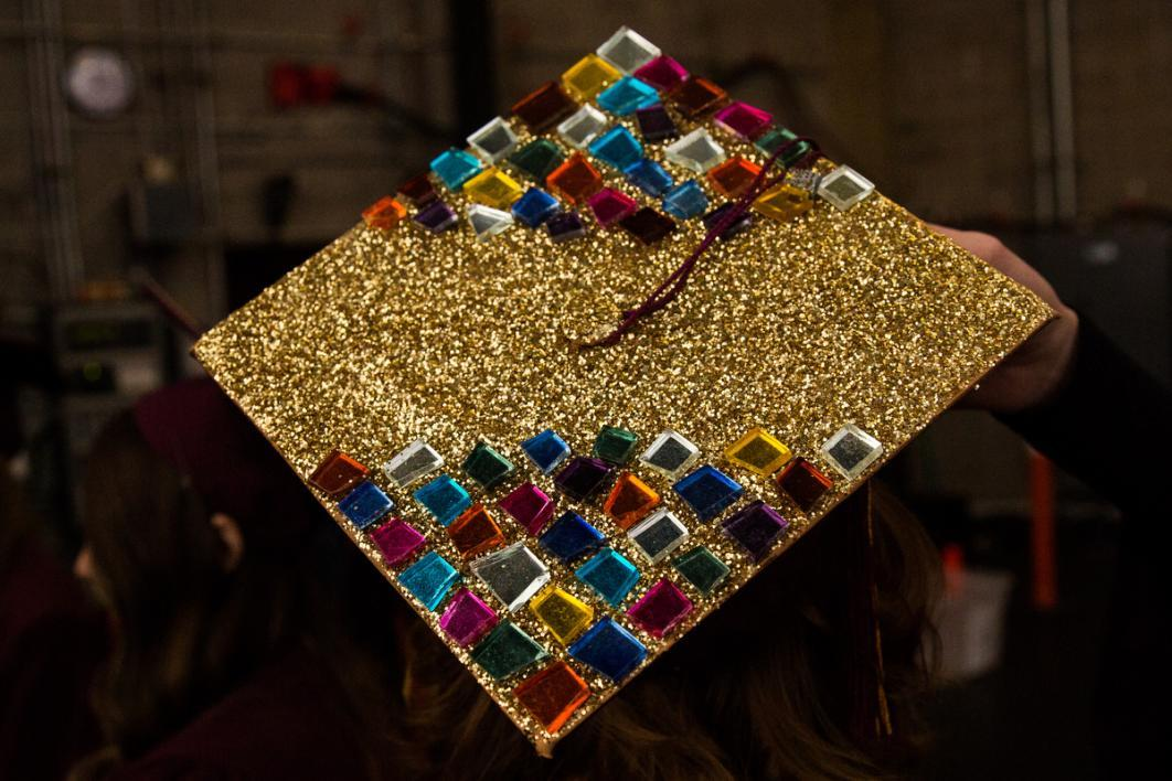A graduation cap is covered in gold and jewels, resembling a prettier tetris board