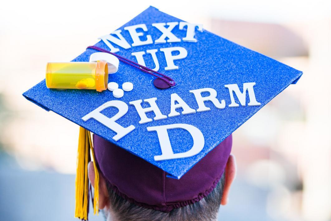 "A graduation cap reads, ""Next up Pharm D,"" and is covered in pills and a pill bottle"