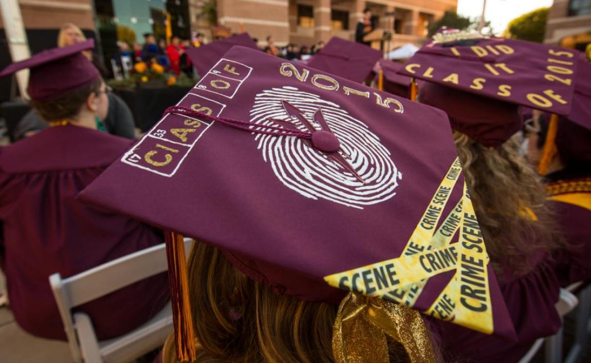 A graduation cap has a fingerprint on top and crime scene tape