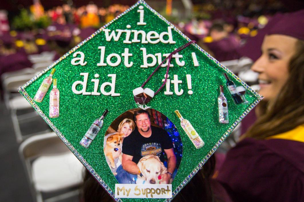 "A graduation cap says, ""I wined a lot but I did it"" and is covered in little wine bottles and a family photo"