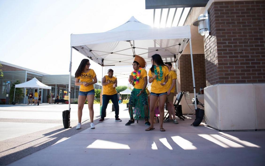 Student helpers dance while waiting for students to arrive to move-in.