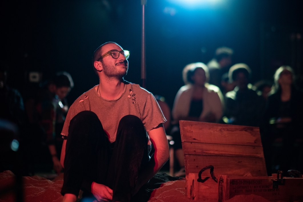 man sitting on the ground with audience behind him