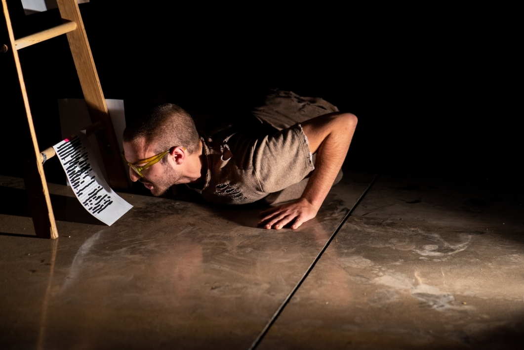 man reading from paper while lying on the floor