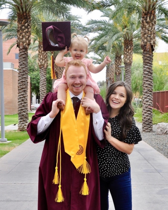 ASU College of Health Solutions graduate Jacob Nicoll smiles and poses with his family, his daughter perched on his shoulders and holding his graduation cap, on Palm Walk at ASU's Tempe campus