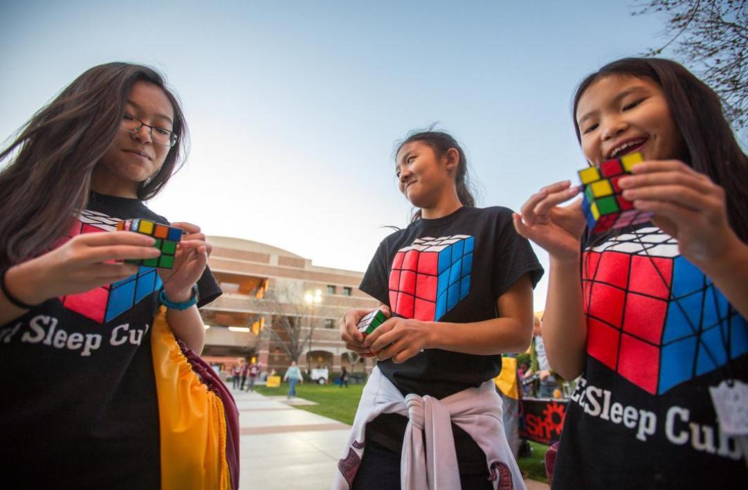 girls holding rubiks cubes