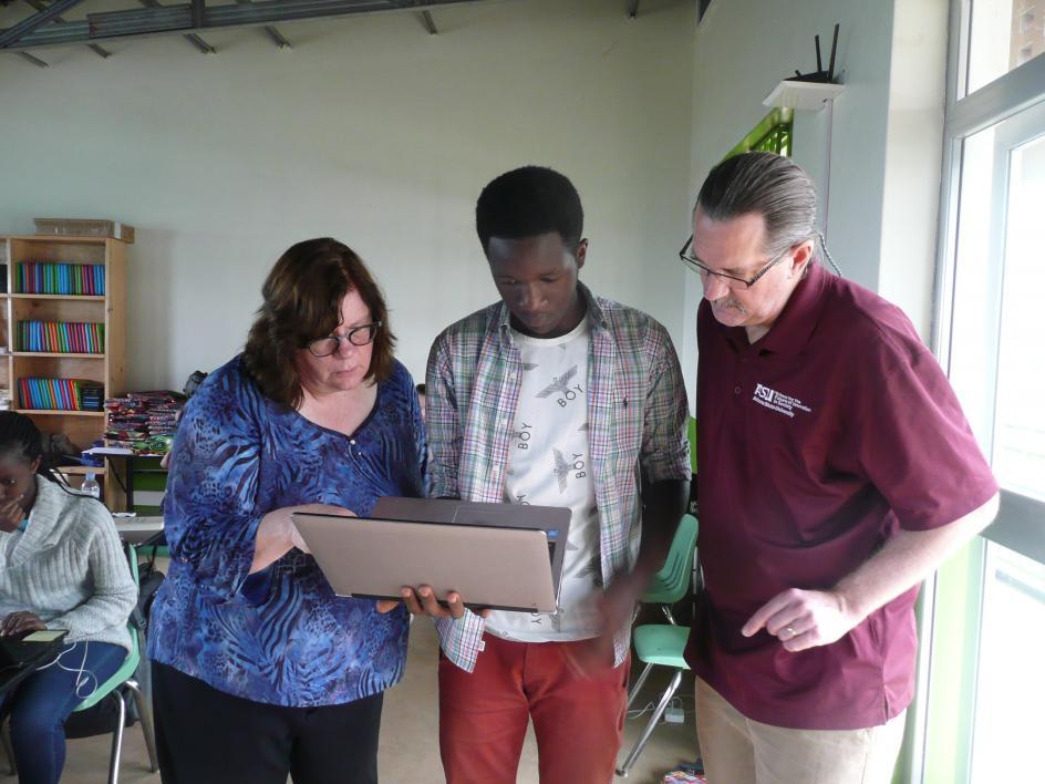 ASU librarians work with a Rwandan student on a laptop