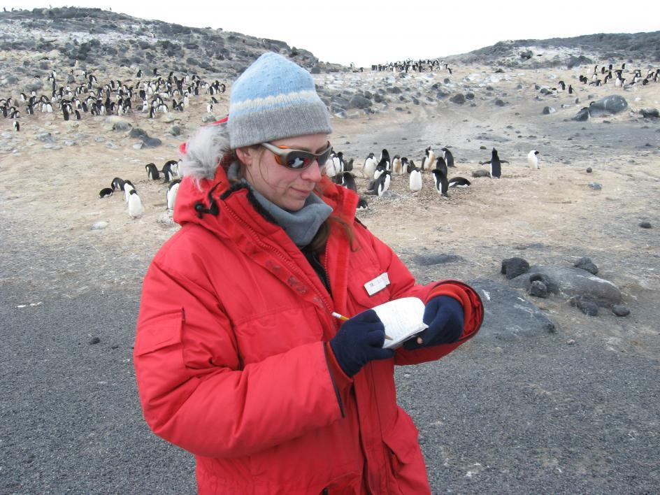 ASU researcher in Antarctica with penguins in the background