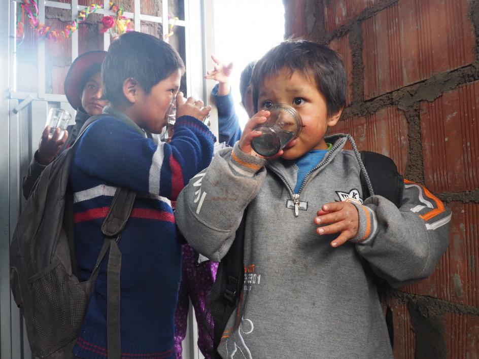 The kids from Huillcapata try the new filtered water during the education event.