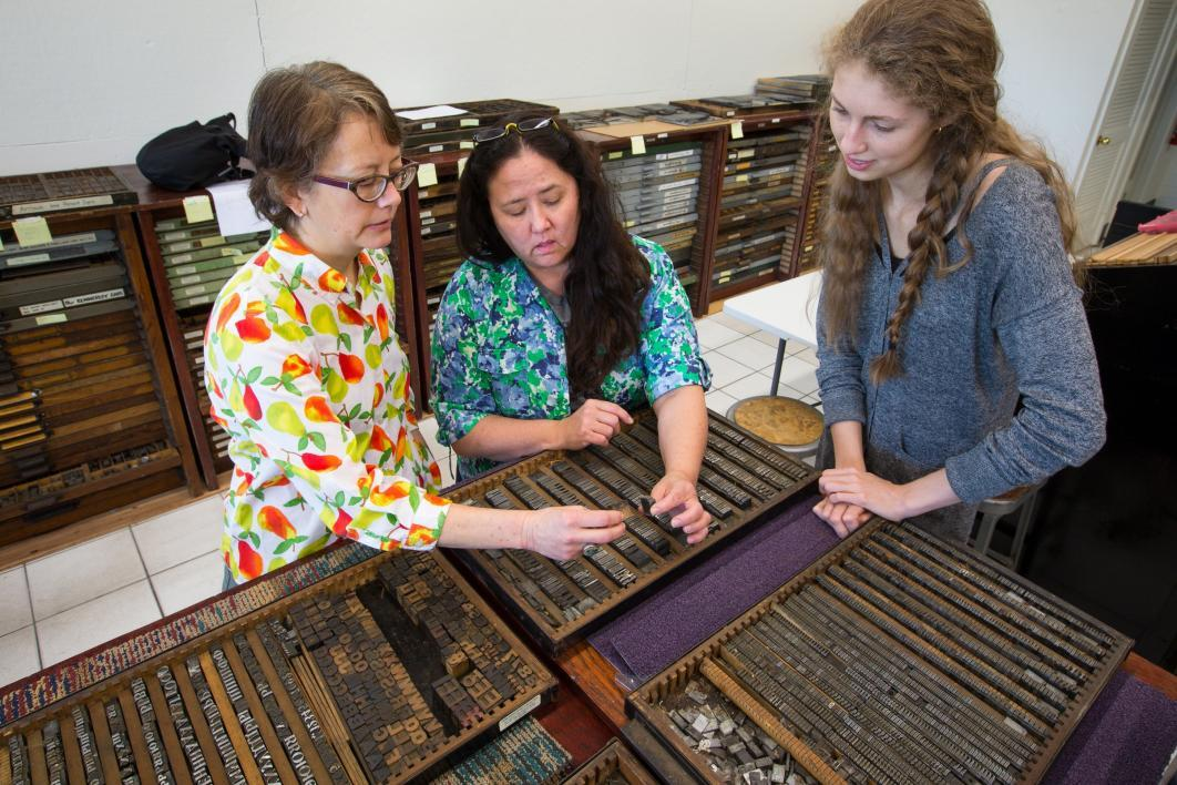 Three women examine print type.