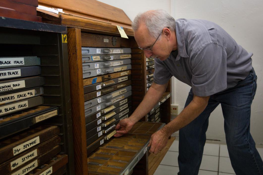 A man opens drawers of printing type.