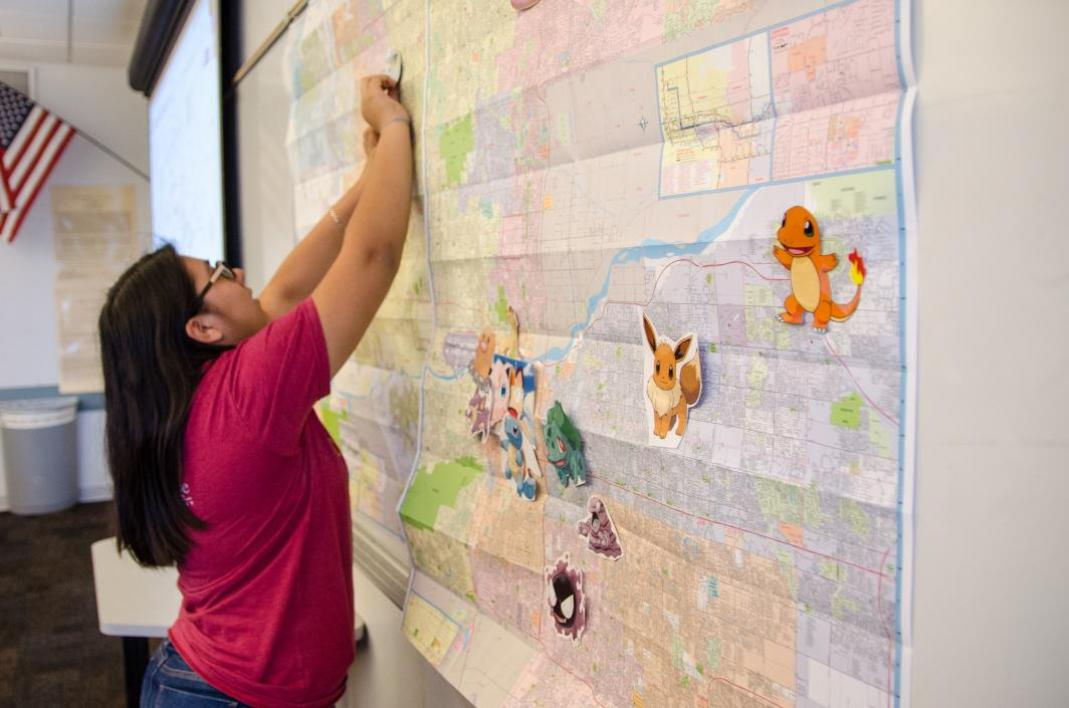 Junior Syndi Flores pins a Pokemon onto a map.