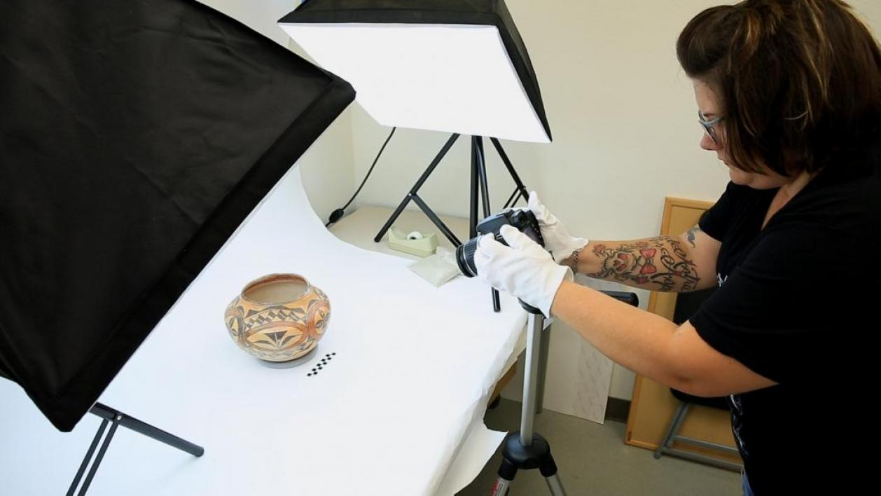 A student documents a pot with a camera.
