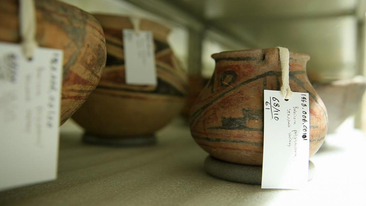 Ancient pots sit on a shelf.