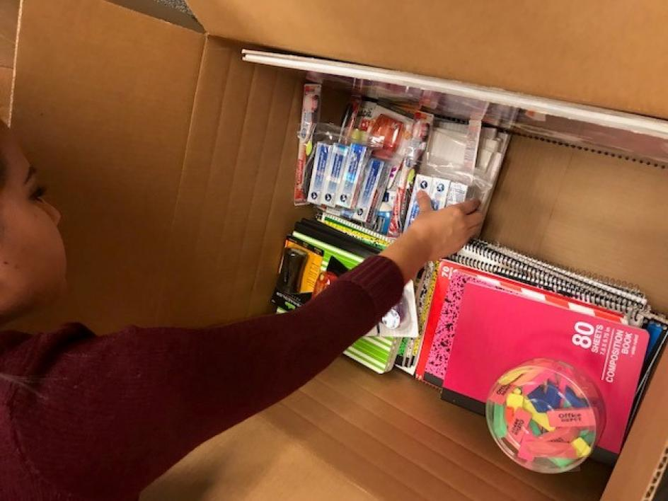 woman packing school supplies into box