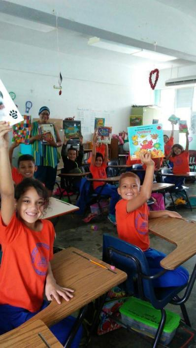 students holding books in classroom